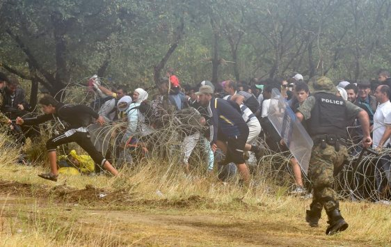 epa04892970 Migrants who wait more then 48 hours on the Greek side of the border line, jump over razer wire to cross in Macedonia near southern city of Gevgelija, The Former Yugoslav Republic of Macedonia, 21 August 2015.Macedonian special police forces arrived yesterday morning and blocked the illegal border crossing between Macedonia and Greece. They don't give permission to the migrants to pass in Macedonia. Macedonian government has declared emergency situation in the south and north border with Greece and Serbia due to rising number of migrants and fugitives from Syria, Afganistan, Iraq, Pakistan and Somalia. From the beginning of the year to mid-June 2015, nearly 160,000 migrants landed in the southern European countries, mainly Greece and Italy, on their way to wealthier countries in Western and Northern Europe, according to estimates by the International Organization for Migration (IOM). EPA/GEORGI LICOVSKI