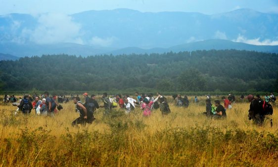 epa04892995 Migrants who waited more then 48 hours on the Greek side of the border line, flee across a field after jumping over razor wire to cross into Macedonia near southern city of Gevgelija, The Former Yugoslav Republic of Macedonia, 22 August 2015.Macedonian special police forces arrived yesterday morning and blocked the illegal border crossing between Macedonia and Greece. They don't give permission to the migrants to pass in Macedonia. Macedonian government has declared emergency situation in the south and north border with Greece and Serbia due to rising number of migrants and fugitives from Syria, Afganistan, Iraq, Pakistan and Somalia. From the beginning of the year to mid-June 2015, nearly 160,000 migrants landed in the southern European countries, mainly Greece and Italy, on their way to wealthier countries in Western and Northern Europe, according to estimates by the International Organization for Migration (IOM). EPA/GEORGI LICOVSKI